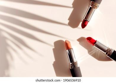 Fashion bunter Lippenstifte Sonnenschirme aus Palmblättern auf beigem Hintergrund, flach gelegen, Draufsicht. Schönheit und Kosmetikhintergrund. Dekorative Kosmetika machen das Design der Beauty-Marke für Frauen aus Lippenstift-Frauen