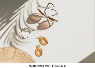Fashion composition with women's accessories on white background with floral shadow. Earrings, sunglasses, bracelet, straw hat on white background. Flat lay, top view french style lifestyle blog