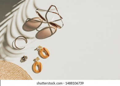 Fashion composition with women's accessories on white background with floral shadow. Earrings, sunglasses, bracelet, straw hat on white background. Flat lay, top view trendy lifestyle blog concept.