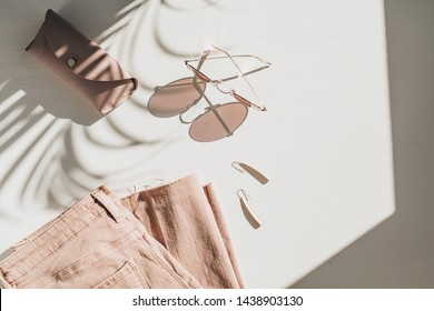 Fashion composition with women's clothes and accessories on white background. Earrings, sunglasses, pink jean culottes on white background. Flat lay, top view lifestyle blog concept.
