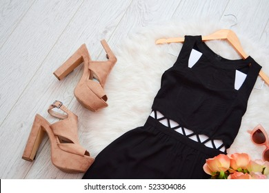 Fashion concept. Black dress and beige shoes on a white background. top view