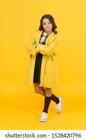 Fashion concept. Charismatic girl on yellow background. Elegant little schoolgirl. Fashionable schoolgirl. Trendy trench. Classy style. Girl adorable stylish modern teenager. Cool schoolgirl.
