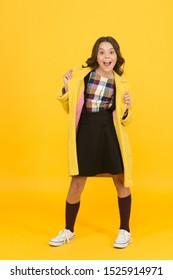 Fashion concept. Elegant little schoolgirl. Fashionable schoolgirl. Trendy trench. Classy style. Girl adorable stylish modern teenager. Cool schoolgirl. Charismatic girl on yellow background.