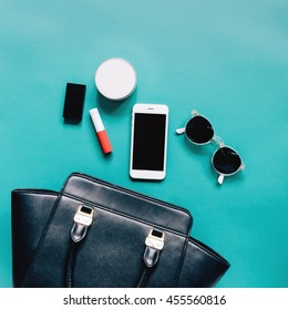 Fashion concept : Flat lay of black leather woman bag open out with cosmetics, accessories and smartphone on green background