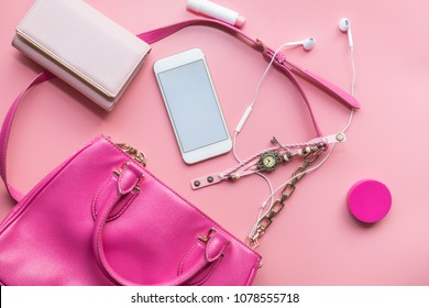 Fashion concept : Flat lay of pink woman bag open out with cosmetics, accessories and smartphone on pink background