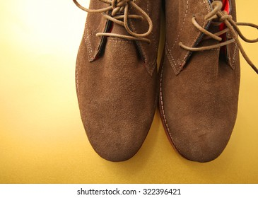 Fashion concept with male brown shoes on golden yellow background