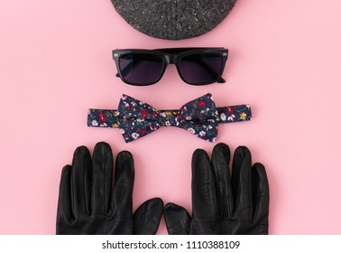 Fashion concept of men's accessories organized on a pastel pink flat lay - black leather gloves, bow tie with floral pattern, sunglasses and an ascot cap