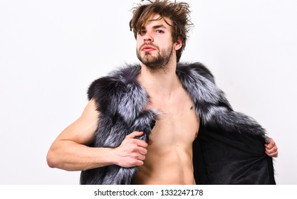Fashion concept. Fashion and pathos. Richness and luxury lifestyle. Sexy sleepy rich macho tousled hair fur vest on white background. Guy attractive fashion model posing fur coat on naked body.
