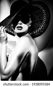 Fashion concept. Portrait of a beautiful woman in big hat and sunglasses in bright contrast light. Female model wearing accessories poses in studio. Professional makeup. Black and white monochrome.