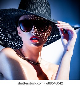 fashion concept - portrait of a beautiful woman in big hat and sunglasses in mixed contrast light