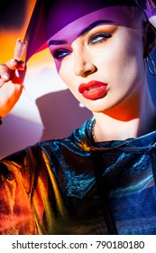 fashion concept - portrait of a beautiful woman in jacket with hood and sunglasses in mixed bright light