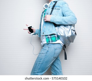 Fashion concept. Young woman with silver backpack on light background, closeup