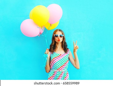Fashion cool girl blowing lips making kiss an air colorful balloons on a blue background