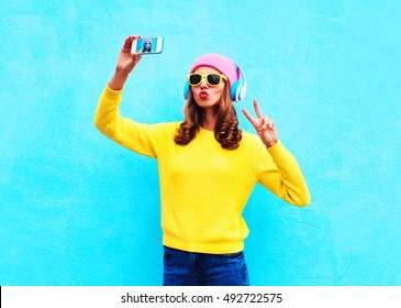 Fashion cool girl in headphones listening music taking photo makes self portrait on smartphone wearing a colorful clothes over blue background