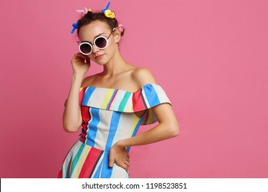 Fashion cool girl posing on pink background. Young hipster woman, curlers in her hair, sunglasses