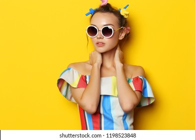 Fashion cool girl posing in sunglasses on yellow background. Young hipster woman, curlers in her hair