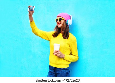 Fashion cool smiling girl in headphones listening music taking photo makes self portrait on smartphone wearing a colorful clothes over blue background