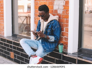 Fashion cool urban african man with smartphone sitting on city street, brick wall background