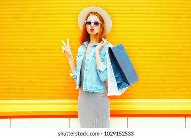Fashion cool young girl makes an air kiss holds a shopping bags in straw hat on orange background