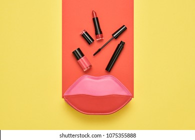 Fashion Cosmetic Makeup Minimal Set. Essentials. Trendy Design Pink Red Clutch Bag. Woman Beauty Accessories. Lipstick Brushes Mascara. Creative. Art Concept Style. Flat lay.
