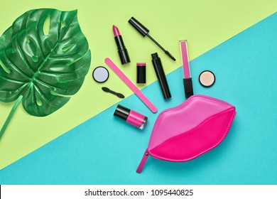 Fashion Cosmetic Makeup Minimal Set. Creative Essentials. Trendy Design Pink Clutch Bag, tropical leaf. Woman Beauty Accessories. Lipstick Mascara. Art Concept Style. Flat lay.