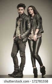 fashion couple in casual leather jackets posing in studio, full body picture