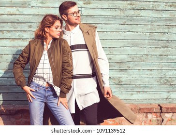 fashion couple in glasses with glasses in green clothes posing on blue wooden wall