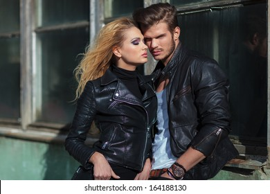fashion couple in leather jackets posing against an old building outdoor