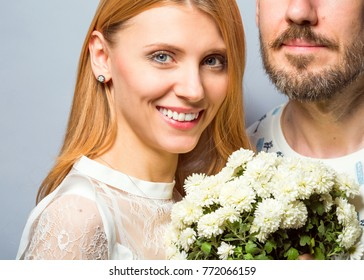 fashion couple in love with a white bouquet of color in the studio posing on a gray background in the day of St. Valentine's Day