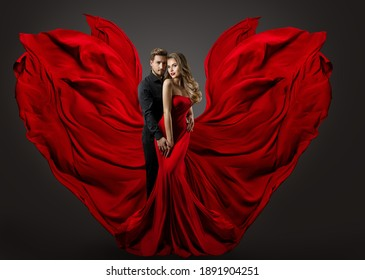Fashion Couple in Love. Woman in fantasy long Red Gown and handsome Man. Flying Silk Fabric as Wings. Studio Portrait