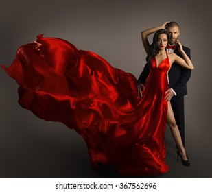 Fashion Couple Portrait, Woman Red Dress, Man in Suit, Long Waving Cloth Flying over Gray