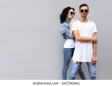 fashion couple posing on a gray background in the street