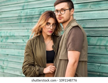 fashion couple standing posing near green wooden wall