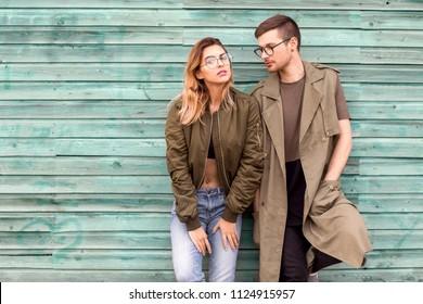 fashion couple standing posing near green wooden wall