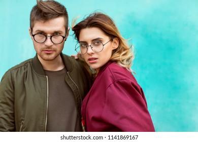 fashion couple standing posing near blue wall