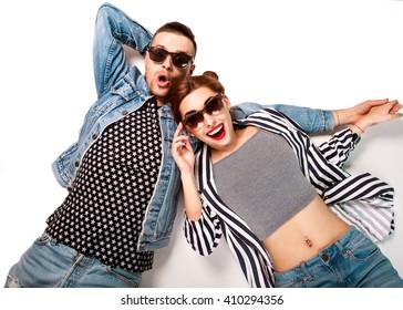Modepaar in Sonnenbrillen liegt auf weißem Hintergrund und lächelt fröhlich und überrascht. Vogue-Stil