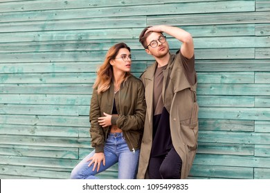fashion couple in their glasses with burgundy clothes posing on a blue wooden wall