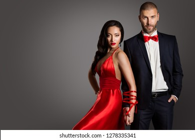 Fashion Couple, Woman and Man Arms Bounded by Ribbon, Models Studio Portrait in Red Dress and Black Suit