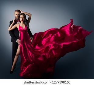 Fashion Couple, Young Beautiful Woman in Flying Waving Dress and Elegant Man, Beauty Studio Shot