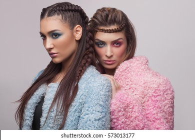 Fashion and creative portrait of two beautiful sexy women with a different eye color makeup
