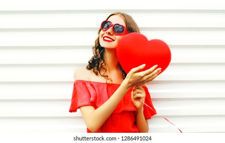 Fashion cute girl in red dress sunglasses with air balloons heart shape over white background