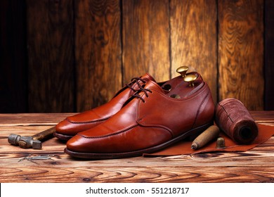 Fashion derby shoes handmade and shoes maker tools (hammer, awl, nails, skien of thread).Wooden background.Concept cobbler