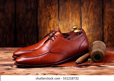 Fashion derby shoes handmade and shoemaker tools awl, nails, skien of thread .Wooden background.Concept cobbler