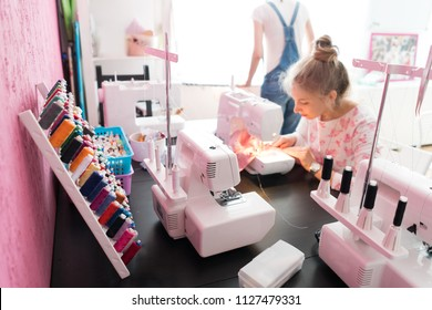 Fashion Design Sewing Machine Concept. Dressmaker woman working with sewing machine.