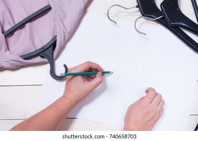 Fashion design sketch. Close up design. Sewing dresses and items for sewing. Sew clothes according to sketches. Centimeter tape, scissors, pattern, thread, hanger