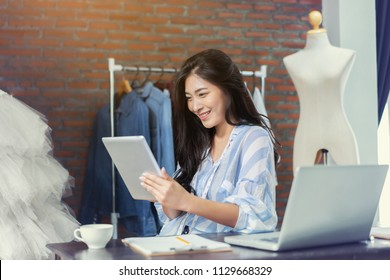 Fashion designer drawing new sketches collection and sent a business e-mail to client. Beautiful young Asian woman working using laptop and digital tablets in Designers Stylish Showroom the workshop