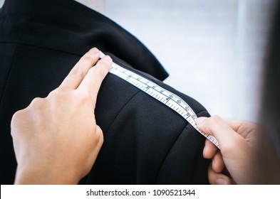 Fashion Designer hand is measuring shoulder with measuring tape