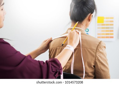 Fashion designer measuring on body part of women for a tailor made dress for a young business girl.