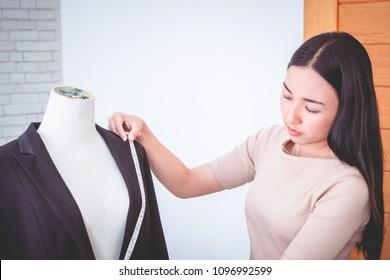 Fashion Designer is measuring shoulder with measuring tape