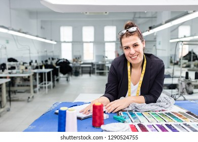 Fashion designer posing with color swatch in textile factory.